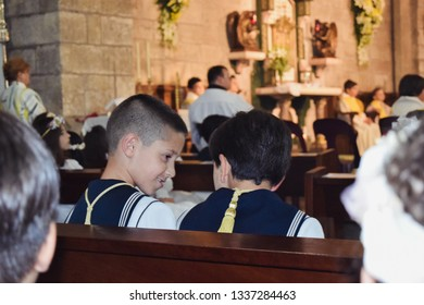 Aviles, Asturias, Spain: 05 15 2016 communion celebration inside a  church, two Boys with the traditional sailor suit sitting on a bench. Praying at mass.