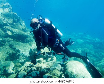 Avlaki,Greece - June 15 2016 : A male scuba diver with a camera shows good buoyancy during a dive. Diving is an adventurous sport in many places around the world.