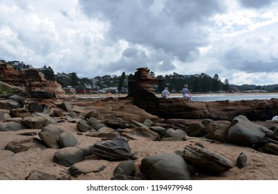 Avoca beach, Australia - Apr 12, 2015. Old couple sitting on a rock. People can enjoy swimming, surfing, sunbathing and relaxing at Avoca beach.