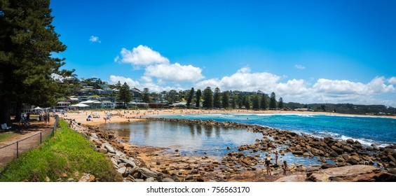 Avoca Beach, Central Coast, Australia - November 12, 2017: Kids playing and People enjoying a sunny day at Avoca Beach on the Central Coast, New South Wales, Australia.