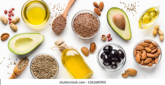 Avocado, almonds, hemp seeds, linseeds, olives and oils over white background, top view. Alternative oils concept
