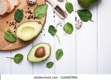 Avocado and baby spinach, bread on a white wooden background. View from above