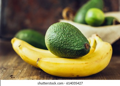 Avocado and banana over brown wooden background