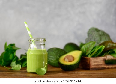 Avocado base home made green smoothies with vegetable leafy greens in a jar standing on a kitchen table, front view