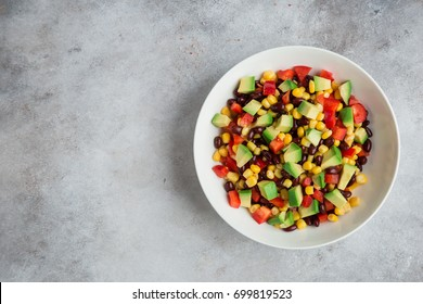 Avocado, black  bean, corn and bell pepper salad in white bowl. Top view, copy space