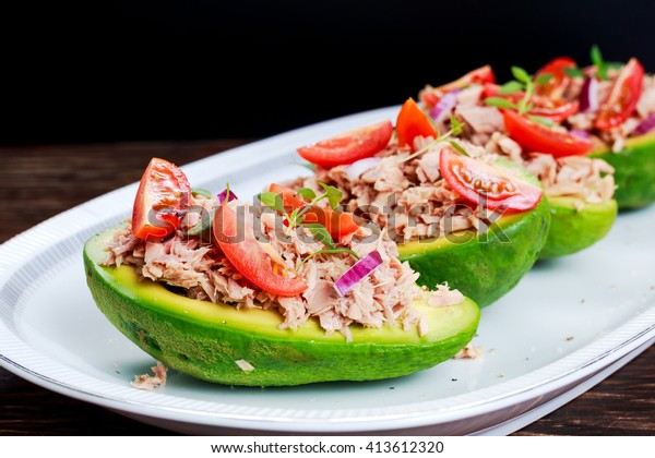 Avocado boats stuffed with tuna, red onion and cherry tomatoes.