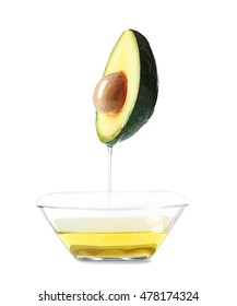Avocado and bowl with avocado oil on white background.