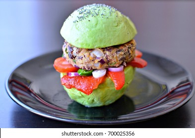 Avocado bun burger with red beans patty and roast bell peppers