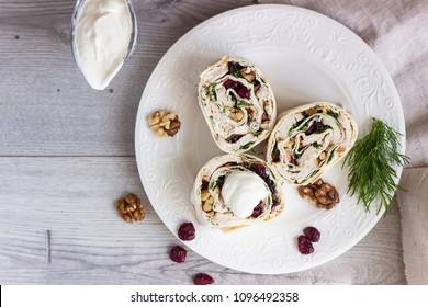 Avocado and chicken salad roll sandwich. Roll sandwich with chicken, avocado, dried cranberries and walnuts. Thin Armenian pita bread or lavash. Snack.