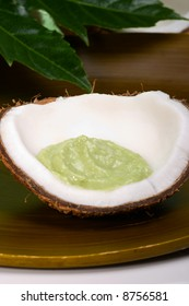 Avocado coconut scrub in coconut shell with tropical leaves. Suited for relaxing and health commercials