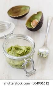 Avocado cream, preserving jar on chopping board