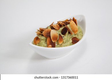 Avocado cream with roasted almond flakes in a white bowl on a light background