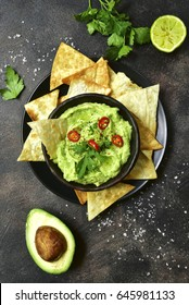 Avocado dip guacamole with tortilla chips in a black bowl on a dark slate or metal background.Top view.