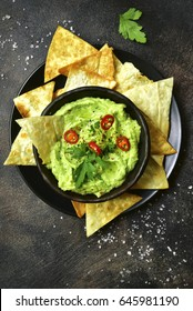 Avocado dip guacamole with tortilla chips in a black bowl on a dark slate or metal background.Top view with copy space.