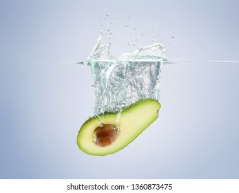 avocado drops in the water scattering a lot of sprays and drops.