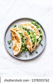 Avocado eggs greens salad paratha flatbread quesadilla on a light background, top view