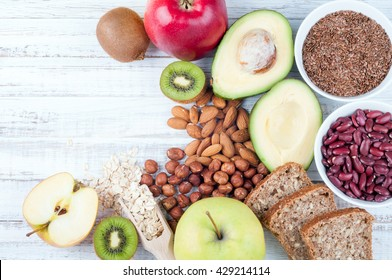 Avocado, flax seeds, whole grain bread, kiwi fruit, nuts, oatmeal, beans and apples on wooden boards. Healthy food. Top view