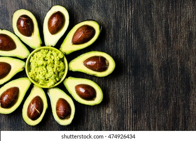 Avocado. Flower made from avocado palta and guacamole bowl on dark background. Guacamole ingredients. Healthy fat, omega 3. Half of avocado. Avocado tree. Top view. Copy space