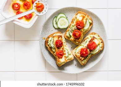 Avocado, Fried Cheese, Fresh Cucumber and Roasted Tomato Toasts, copy space for your text