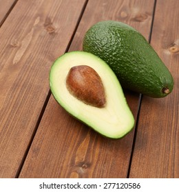 Avocado fruit lying over the brown colored wooden board surface as a background composition