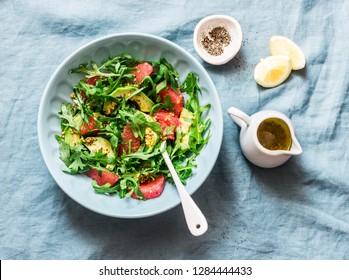 Avocado, grapefruit, rocket salad with mustard olive oil salad dressing on blue background, top view. Vegetarian diet food concept