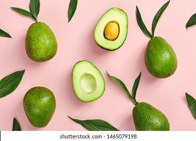 Avocado and green leaves pattern on pink background. Top View. Pop Art design, creative summer food concept. Green avocadoes, eco and healthy food minimal flat lay. Banner of organic food minimal