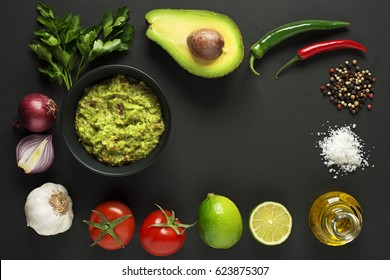 Avocado guacamole with fresh ingredients on black table