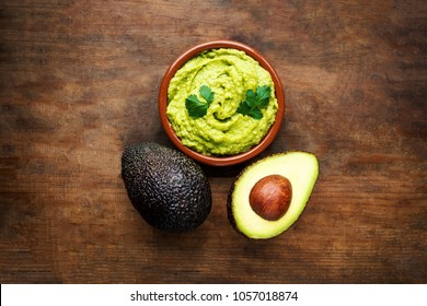 Avocado with guacamole sauce on a dark wood background. Half and whole avocadoes close up. Top view. Copy space