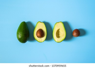 Avocado with half and seed on light blue background. Hard light
