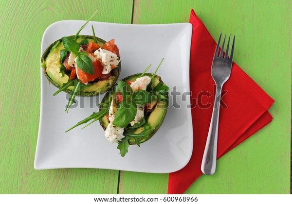 avocado halves with cheese , tomatoes and basil, on green background with red napkin on the side