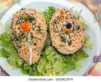 Avocado halves filled with a salmon cream, richly decorated with herbs and caviar on a bed of lettuce, all on a round plate in top view and close-up.