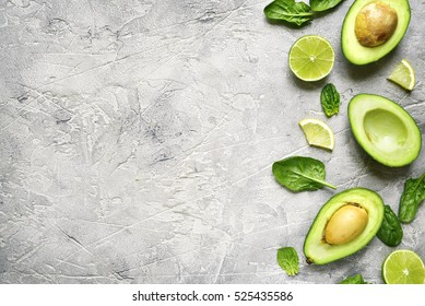 Avocado halves with lime slices and baby spinach leaves on a grey concrete,stone or slate background.Top view with copy space.