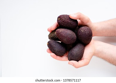 Avocado in the hands of a man on a light background. Healthy food and lifestyle. For lovers of avocado and vegetarians. Avocado closeup. Ready to eat. Nutrition and diet concept. Eco product