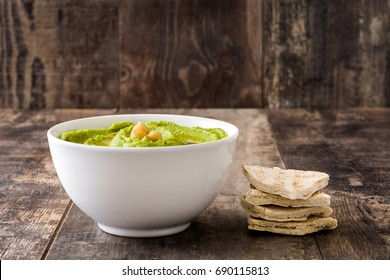 Avocado hummus in bowl on wooden table