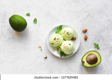 Avocado Ice Cream on white stone background, top view, copy space. Green vegan avocado or pistachio gelato ice cream with almonds and mint leaves.