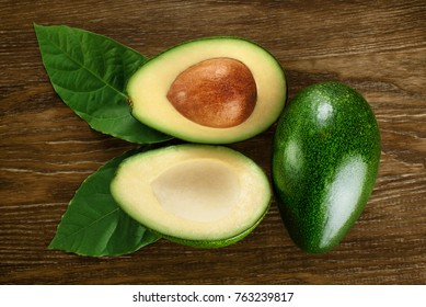 Avocado with leaves on a dark wooden background. Top view.
