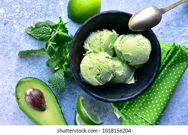 Avocado lime mint ice cream in a black bowl over light grey slate, stone or concrete background.Top view .