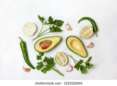 avocado, lime, onion and spices on a light background. view from above.