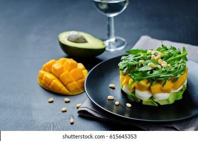 Avocado mango arugula pine nuts Mozzarella salad. toning. selective focus