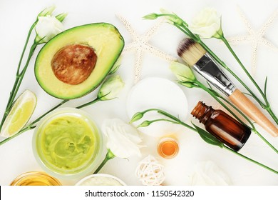 Avocado mask for beautiful skin and hair treatment. Facial mask in jar with essential oils and white blossom, healthy ingredients viewed above on table.
