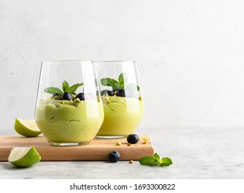 Avocado mousse. Vegetarian sugar free creamy dessert made of avocado, pistachio nuts, honey and lime juice. Healthy sweets with blueberry and green leaves of fresh mint. Copy space, place for text.