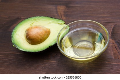 Avocado oil in bowl on wooden table