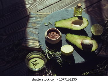 Avocado oil domestic beauty treatment use. Bottle of oil-based tonic, green plant decor on towel and fresh fruit. Blur wooden studio background. Some spices. Oil. Avocado.