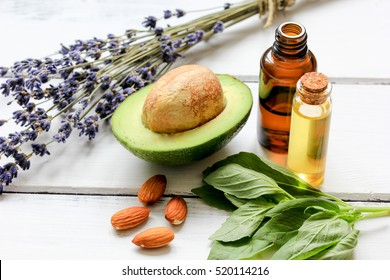 avocado oil for handmade cosmetics with herb on wooden background