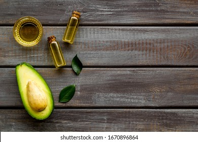 Avocado oil - ingredient for cosmetics - on woode background top-down frame copy space