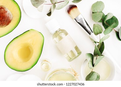 Avocado oil natural skin care & hair treatment. Green organic ingredients & essential oil cosmetic bottle, top view white table.