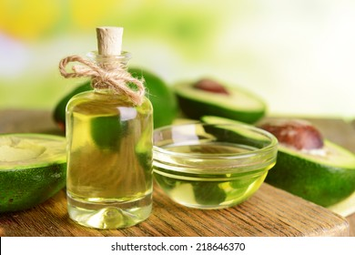 Avocado oil on table on light background