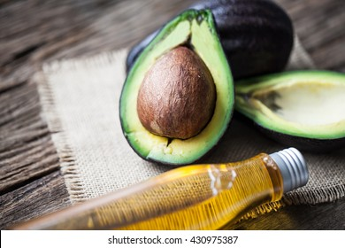 avocado and avocado oil on wooden background