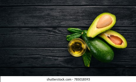 Avocado and avocado oil on a wooden background. Top view. Free space for your text.