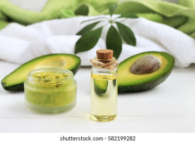 Avocado oil skin & hair care home spa. Bottle of oil, jar of mask, bathroom towel. Green and white
